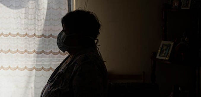 Covid patient wearing mask in a dark room
